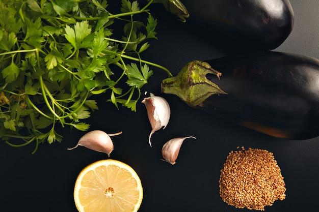 Stilleven van aubergines, peterselie, citroen, knoflook en sesamzaadjes op een zwarte achtergrond