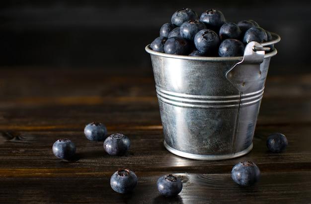 Stilleven van bluberry in de kleine emmer op houten tafel