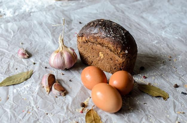 Stilleven van brood, eieren, knoflook en kruiden.