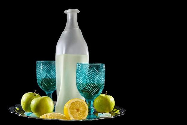 Stilleven van een fles limonade, glazen en citroenen op zwarte achtergrond