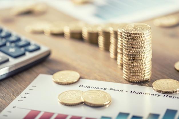 Stilleven van euromunten met groei-efect businessplan en rekenmachine.