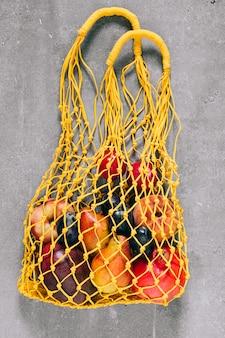 Stilleven van gele biologisch afbreekbare boodschappentas met rauw fruit