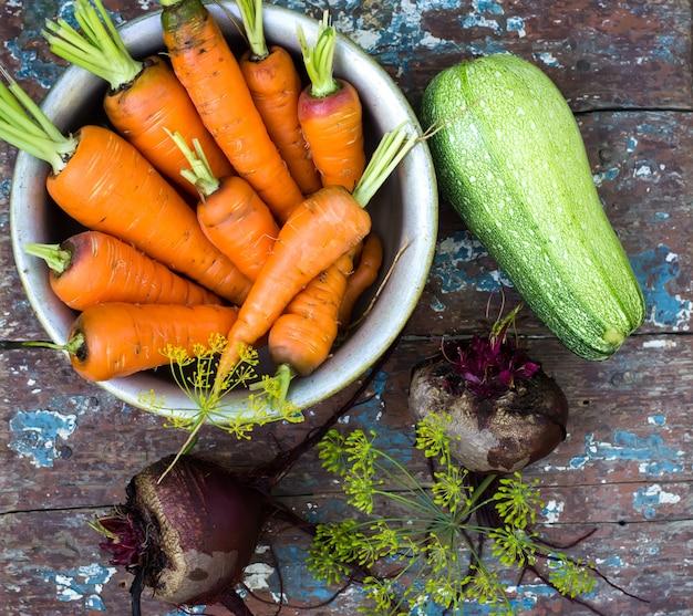 Stilleven van groenten, wortelen, bieten, courgette, kruid op houten tafel
