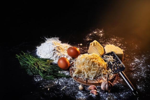 Stilleven van het proces van het maken van kaasballetjes met knoflook en dille op een zwarte ondergrond.