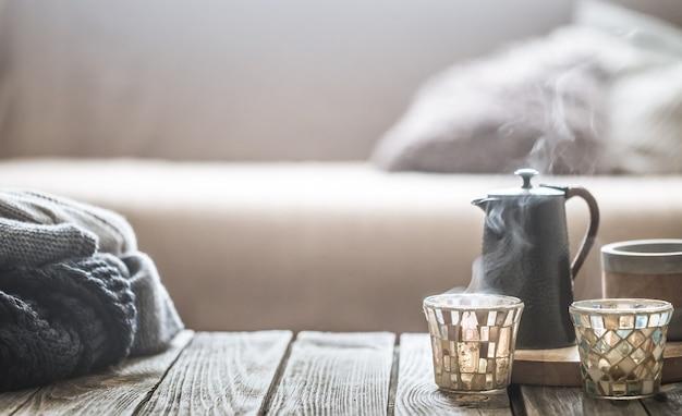 Stilleven van huis interieur op een houten achtergrond met een kleine waterkoker en een mooi glas, home comfort concept