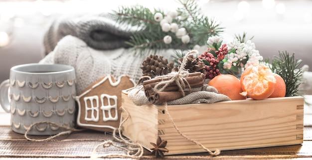 Stilleven van kerstversieringen, een mooie schaal met fruit en feestelijke kruiden aan de kerstboom en gebreide kleding