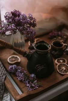 Stilleven van lila bloemen, koffie op houten dienblad