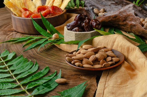 Stilleven van noten en gedroogde vruchten op een houten tafel met varenbladeren