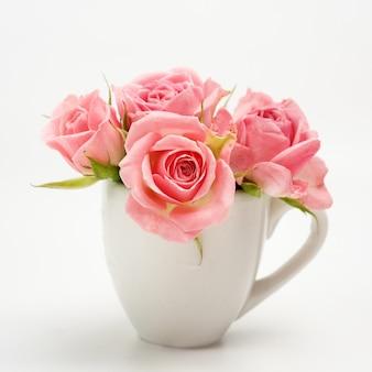 Stilleven van roze roos in keramische beker