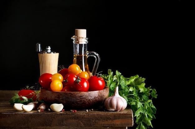 Stilleven van tomaten, knoflook en olijfolie op houten planken.