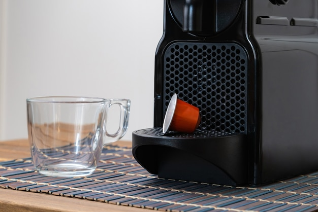 Stilleven van verfrissende espressocapsule en kopje naast koffiemachine.