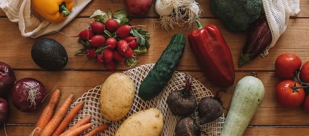 Stilleven van verse groenten met stoffen zakjes op een natuurlijke houten basis