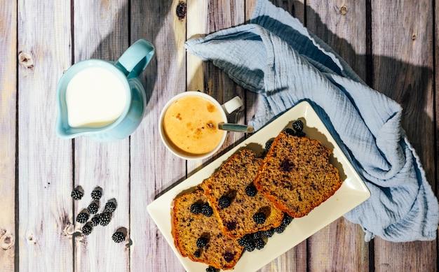 Stilleven van wilde fruitcake met kopje melk met cacao en melkkannetje.