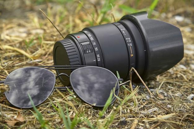 Stilleven van zonnebrillen en een vintage optiek voor het maken van foto's, het vastleggen van de details van de apparatuur die een fotograaf meebrengt.