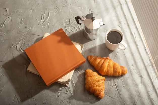 Stilleven voor een aangename koffie in de ochtend turkse kop en croissants met twee boeken op tafel