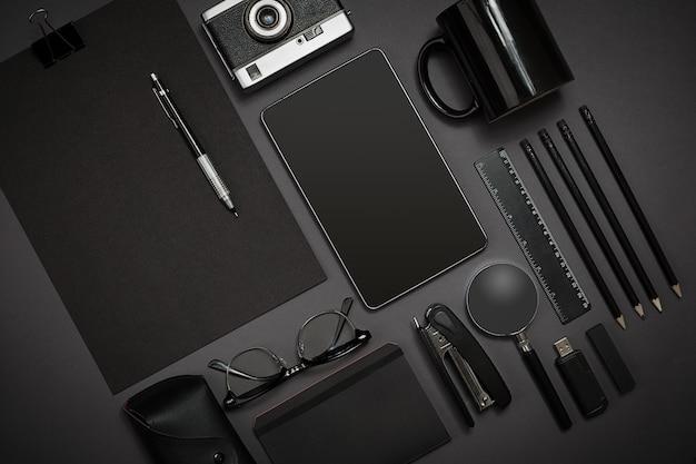 Stilleven, zaken, kantoorbenodigdheden of onderwijsconcept: bovenaanzicht van notitieblok, mobiele telefoon en koffiekopje op zwarte achtergrond, klaar om toe te voegen of te bespotten