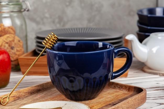 Stillevenfoto van lege theekop met honingslepel. keukentafel close-up