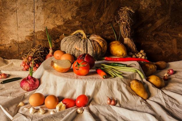 Stillevenfotografie met pompoen, kruiden, kruiden, groenten en vruchten.