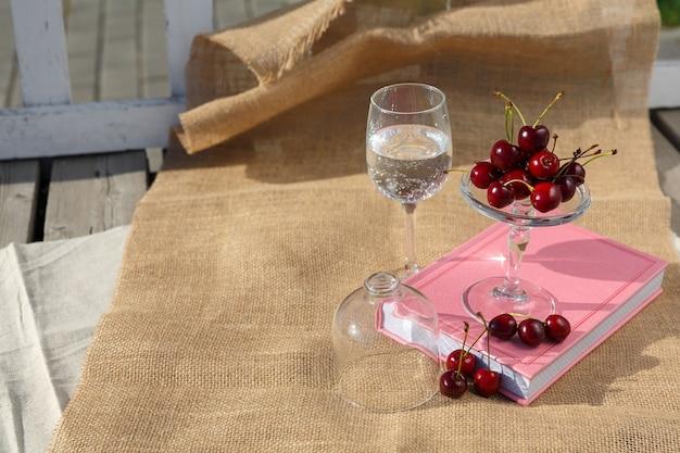 Stillevenvoedselfoto servicebord op voet en minikoepel met kersenbessen is op boek en jute