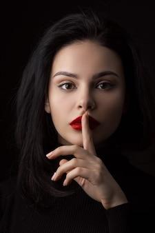 Stilte wees stil vrouw geïsoleerd op zwart mooi meisje met vinger op haar lippen