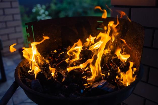 Stock beeld van houtskool vuur grill, close-up met live vlammen.