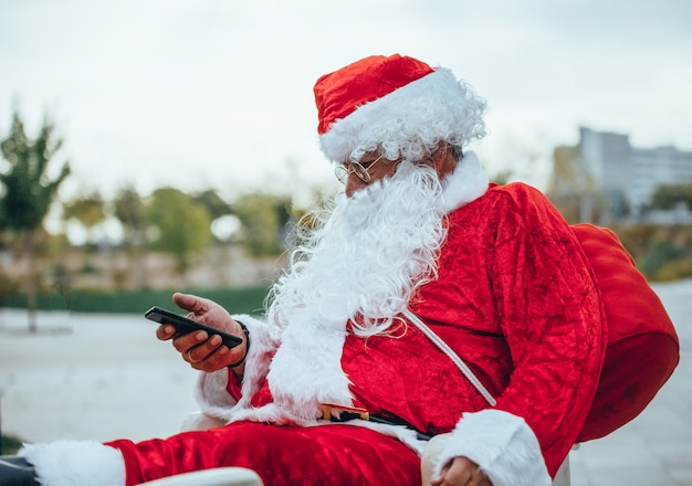 Stock foto van de kerstman praten met een mobiele telefoon met een park achter ongericht