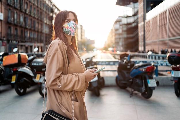 Stock foto van een jonge blanke vrouw met behulp van haar smartphone in de straat. ze draagt een gezichtsmasker vanwege covid19.