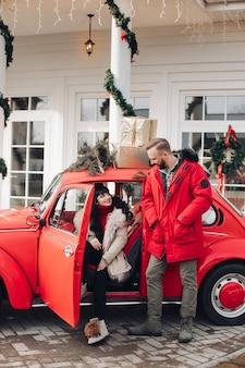 Stock foto van een mooie vrouw en knappe man in vintage rode auto met geschenken bovenop.