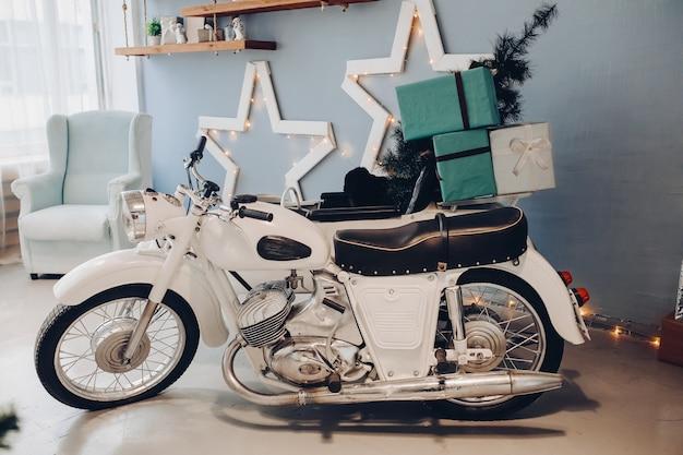 Stock foto van witte motorfiets met miniatuur kerstboom en verpakt kerstcadeautjes in de wieg. sfeervol interieur voor eerste kerstdag. 2020 nieuwjaar.