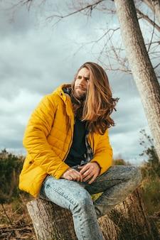 Stock fotografie van een aantrekkelijke blonde man met een gele jas