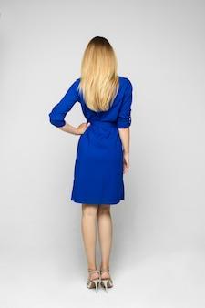 Stock studio achteraanzicht van een blonde jonge volwassen slanke vrouw in indigo jurk van gemiddelde lengte en sprankelende hakken.