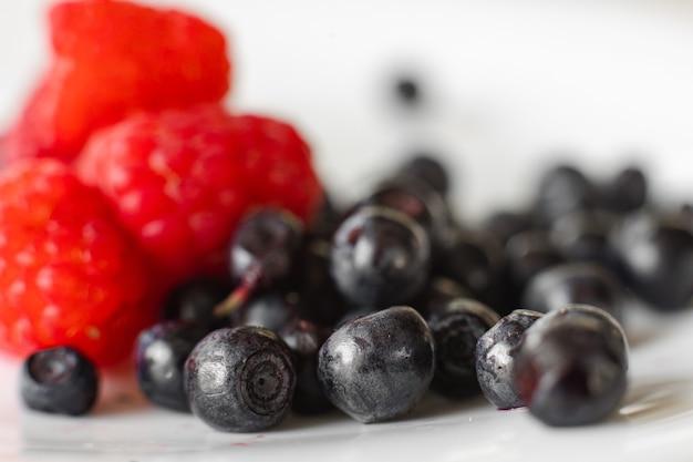 Stockfoto close-up van zwarte bessen bessen geïsoleerd op een witte achtergrond en ongericht rode frambozen. verschillende verse bessen op wit. selectieve aandacht.