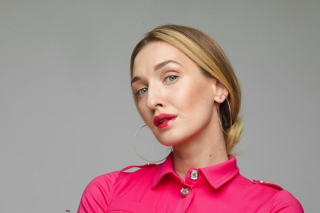 Stockfoto headshot van een prachtige vrouw met een perfecte huid, heldere lippen en natuurlijke make-up met gouden oorbellen en een levendige roze blouse. isoleer op grijze achtergrond.