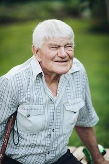 Stockfoto portret van een oude blanke man in geruit hemd met twee borstzakken met een kruk onder een oksel zittend op een bankje buiten en glimlachend in de camera.