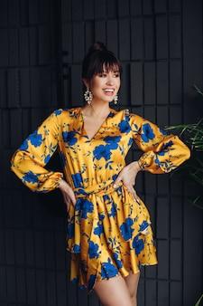 Stockfoto portret van een prachtige brunette in een prachtige gele en blauwe overall of pak bewegend en glimlachend naar beneden. mode portret.