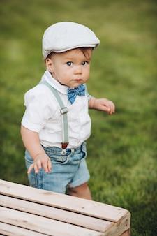 Stockfoto portret van een schatje in hoed, shirt, korte broek en strik met bretels camera kijken tijdens het wandelen op groen gazon in de achtertuin. kijkend naar de camera met nieuwsgierigheid. Gratis Foto
