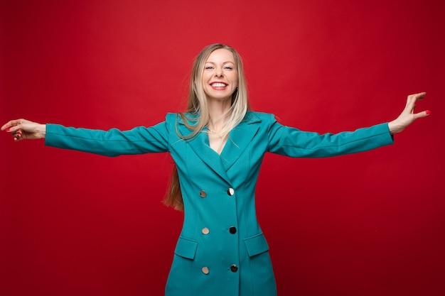 Stockfoto portret van gelukkige joviale blonde vrouw in casual double-breasted jurk of jas met uitgestrekte armen glimlachend in de camera. plezier hebben in de studio op rode achtergrond.