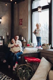 Stockfoto portret van gelukkige ouders knuffelen op de bank. hun dochtertje staat op de vensterbank met speelgoed in handen. ze glimlachen naar de camera.