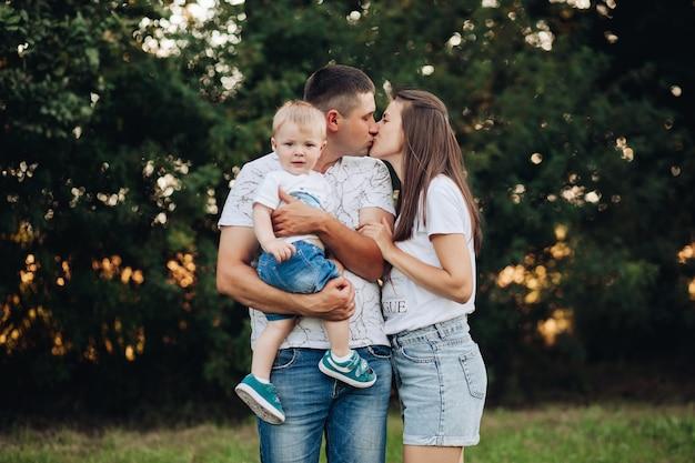 Stockfoto portret van kussende ouders met een babyjongen die naar de camera kijkt. kleine jongen zittend op vaders arm en kijkend naar de camera terwijl zijn ouders zoenen.