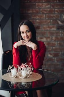 Stockfoto portret van mooie brunette jonge volwassen meisje in rode jurk zittend aan glazen ronde tafel met decoratieve kaarsen. mooie vrouw zitten in café tegen bakstenen muur.