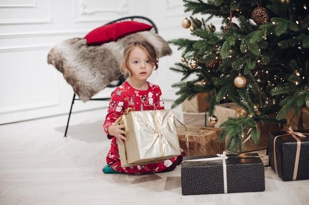 Stockfoto portret van schattig meisje in rode jurk met feestelijke print met prachtig verpakt gouden cadeau in handen zittend op de vloer naast versierde kerstboom met slinger.