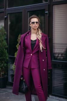 Stockfoto portret van stijlvolle zakenvrouw met vlecht in zonnebril, modieus fel paars pak en trenchcoat over haar schouders dragen. ze houdt een luxe leren tas in haar hand.