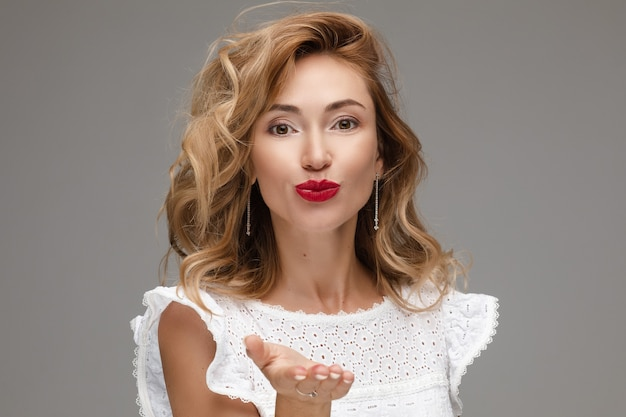 Stockfoto studio portret van een prachtig jong volwassen kaukasisch model met rommelig blond haar en rode lippen in romantische witte blouse die luchtkus naar de camera stuurt. isoleer op grijs.