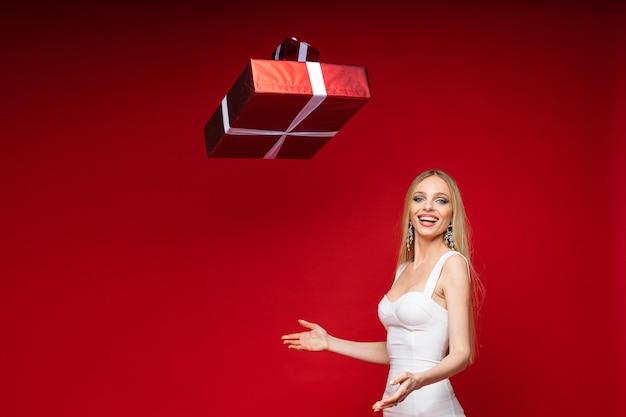 Stockfoto van aantrekkelijke joviale blonde vrouw in cocktailjurk en oorbellen die kerstcadeautjes in de lucht gooien en glimlachen naar de camera. geïsoleerd op rode muur. ruimte kopiëren.