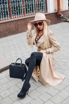 Stockfoto van een prachtig zelfverzekerd blond model met modieuze beige trenchcoat, beige hoed en zwarte zonnebril met leren handtas in de stad.