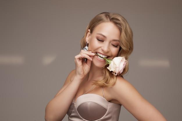 Stockfoto van een prachtige blonde vrouw met blauwe ogen en natuurlijke make-up die een roze sluier draagt en een fragiele roze roos vasthoudt. bruid concept.