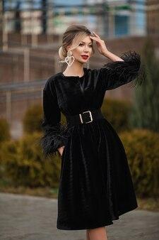 Stockfoto van een prachtige jonge volwassen vrouw met rode lippen, modieuze oorbellen in de vorm van een hart, gekleed in een elegante dure zwarte bontjas met riem.