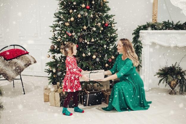 Stockfoto van liefhebbende moeder in groene jurk die haar dochtertje in pyjamajurk een kerstcadeau geeft. ze zijn naast prachtig versierde kerstboom onder sneeuwval.