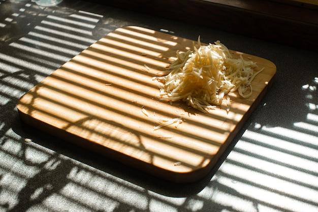 Stockfoto van stapel verse gele geraspte kaas op houten snijplank op keukentafel bedekt met jaloezieën schaduw. strepen van jaloezieën op het raam gieten over boord met geraspte kaas.
