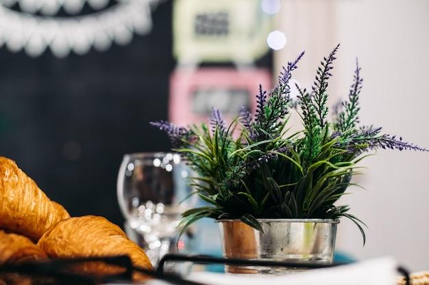 Stockfoto van verse lavendelbloemen in stalen zilveren pot naast versgebakken croissants.